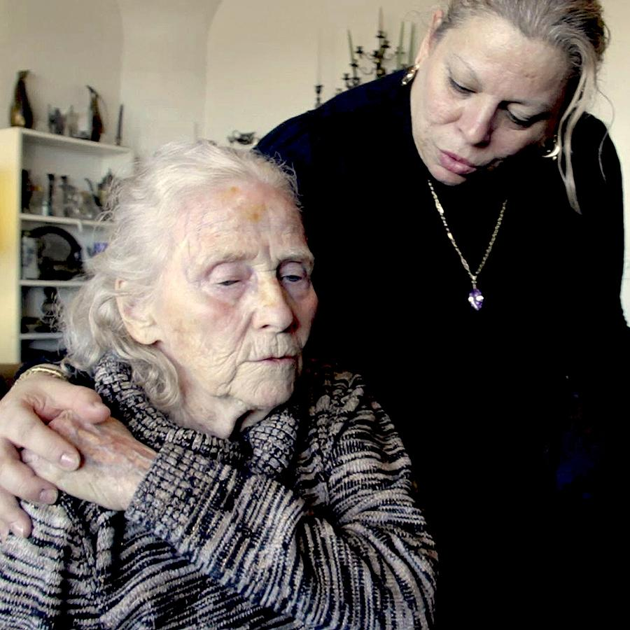 A care worker looks down at an elder woman. They hold hands, and the elder woman's eyes are downcast.