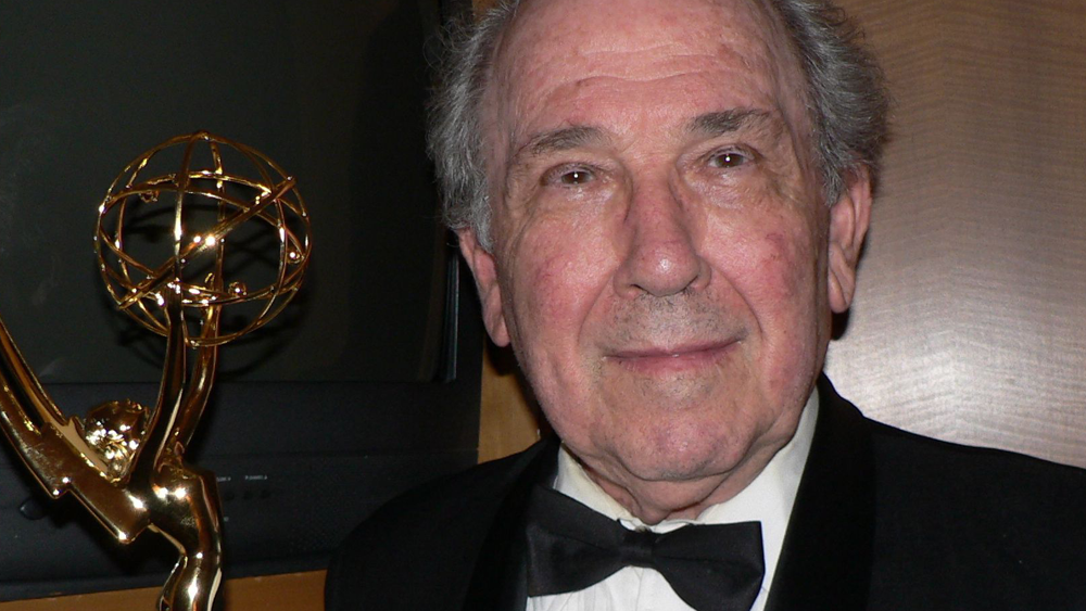 Filmmaker Robert Richter looks at the camera with a slight smile, wearing a black tux. A gold Emmy statue is to his left.