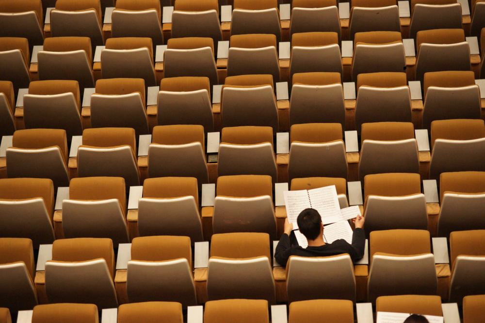 Overhead view of empty, orange seats in an auditorium style classroom. One student in the lower right sits and reads from two open notebooks.