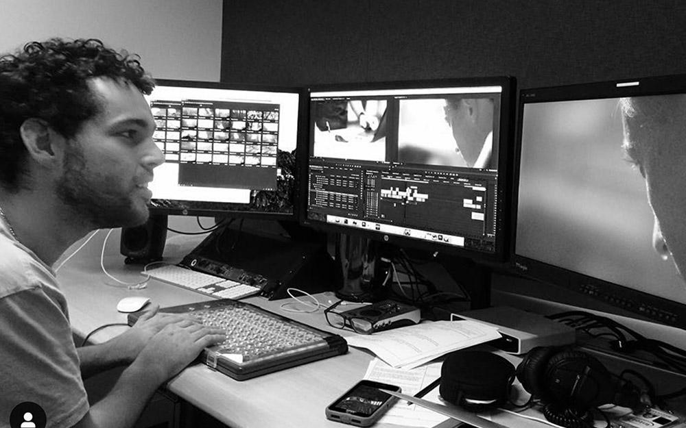 New Day Filmmaker Reid Davenport is sitting at a desk with his hands on a keyboard in a video editing room. He faces three video monitors and has a small smile on his face.
