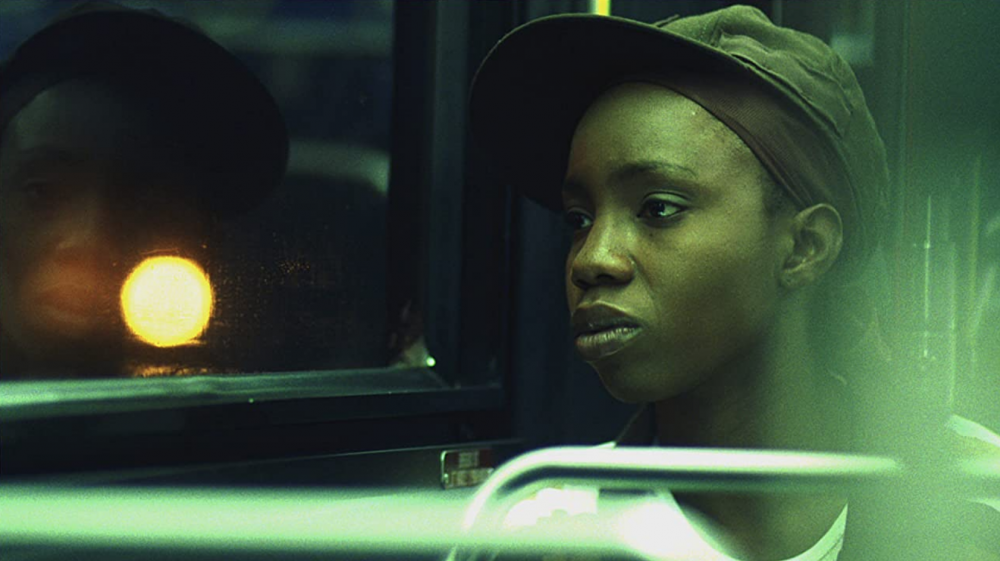[Image Description: A close up image of a Black youth sitting in a bus with their face reflected on the bus window. A harsh white street light obscures their reflection against the dark night background. They appear pensive]