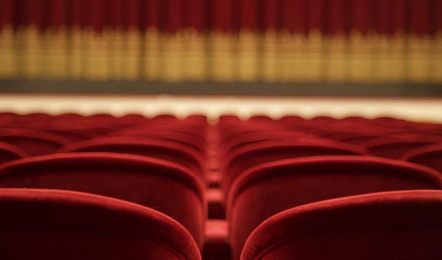 In this empty theatre, we see rows of velvet chairs and an out-of-focus stage.