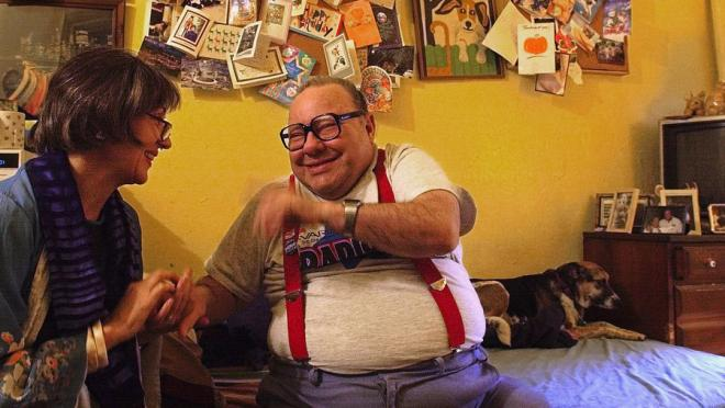 [Image Description: An image of Larry Selman, a community activist and fundraiser who has an intellectual disability, and filmmaker Alice Elliot seated, holding hands, talking and laughing in a bedroom. Behind them is a seated dog, a poster board filled with cards, a dresser with an old TV on top and framed photos]