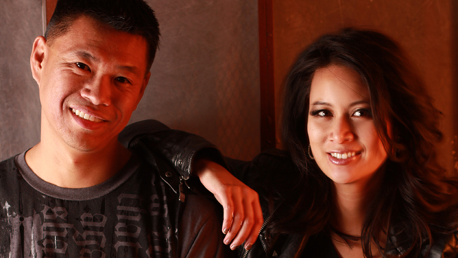 New Day husband and wife filmmaking team Baldwin Chiu and Larissa Lam look directly in the camera smiling softly. Larissa is wearing a leather jacket and has her arm on Baldwin's shoulder. He is wearing a black shirt with writing on it. They are bathed in red lighting.