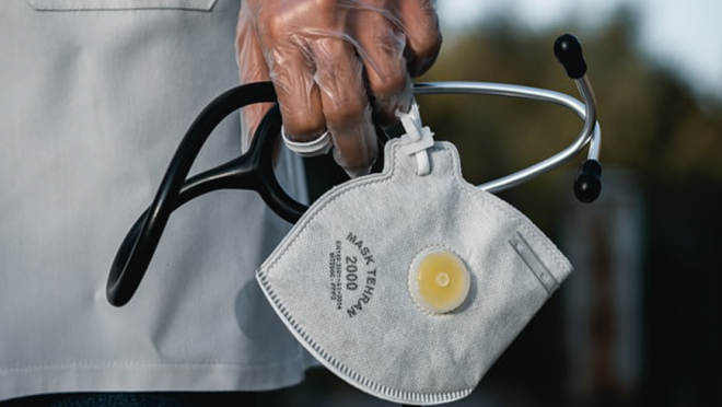 A medium shot of a hand holding a mask and stethoscope. In the background is the torso of a person wearing a white doctor's outfit.