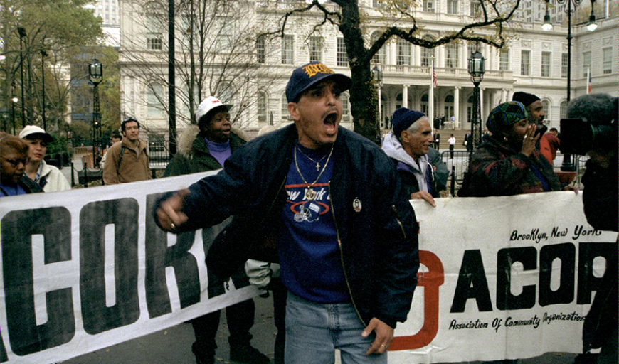 Outside on a cold day, a protest led by workers of color demonstrating and yelling chants.