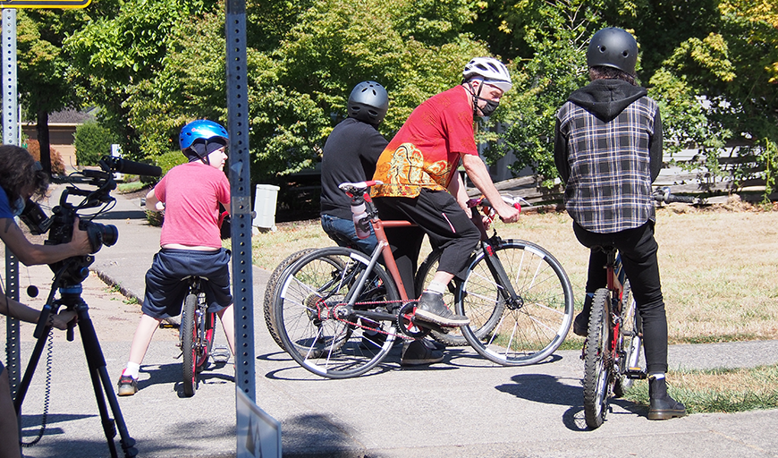 On the left edge of the frame, Cheryl, in a medical mask, bends over a camera mounted on a tripod and films Karl and his three sons as they wait to ride their bicycles. Karl also wears a mask. It is a summery day with sunshine and green trees in the background.