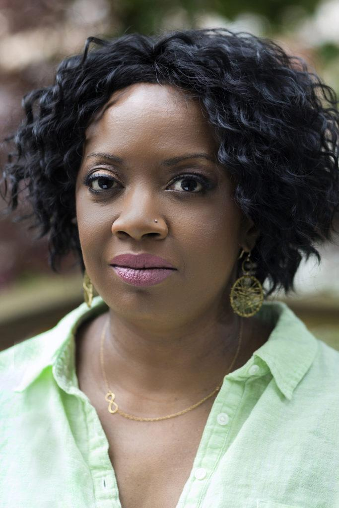 A headshot of New Day Filmmaker Faith Pennick, an African-American woman with wavy shoulder length hair and a pierced nose. She looks directly at the camera with a neutral expression.