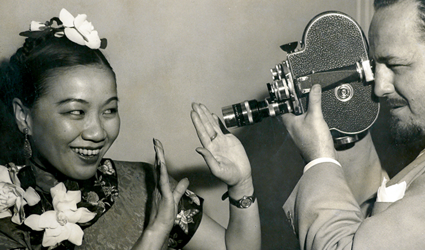 Chinese-American filmmaker Li-Ling Ai wears a silk patterned dress with flower blossoms pinned by the neckline and in her pulled-back hair. She smiles and playfully holds up her hand to create a frame around her face. White photograph Rey Scott wears a light linen suit and holds a film camera to his eye, the lens just an inch from her hands. The photograph is black and white