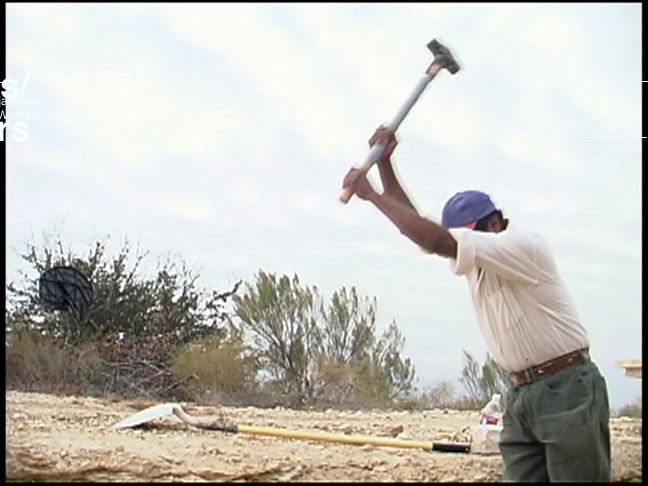 A Latinx man with dark skin and shirt sleeves rolled up on a dusty terrain. He holds a pick axe and is just beginning to lower it to strike.