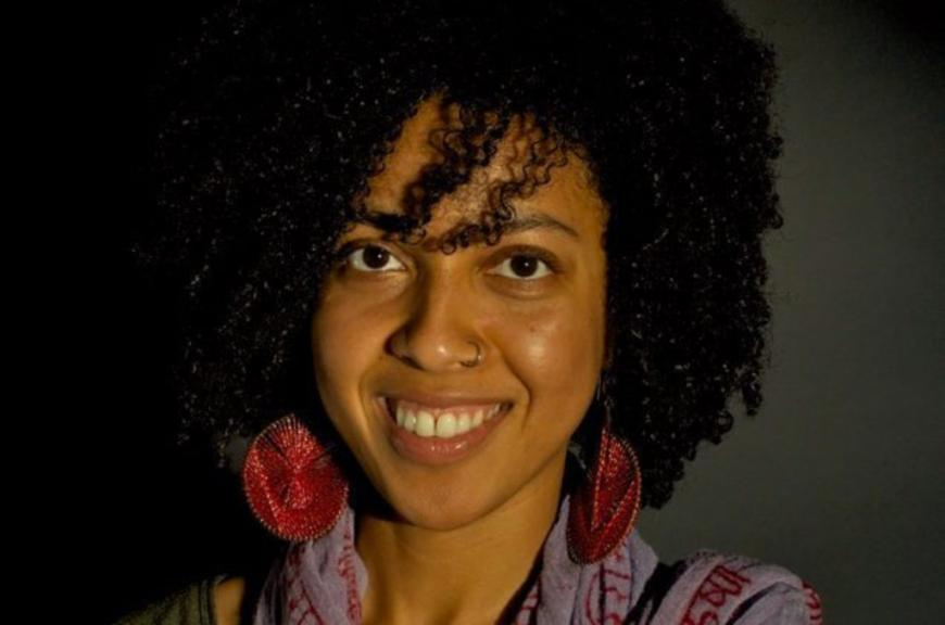 A headshot of New Day Filmmaker Najma Nuriddin, an African-American woman with wavy shoulder length hair and large red earrings. She looks directly at the camera and smiles widely.