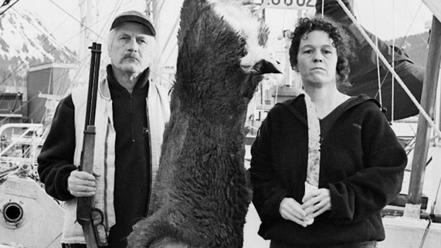 In this black and white photo, a woman and man stand on a dock with a dead, hanging deer between them. The man holds a hunting rifle. Behind them is a boat.