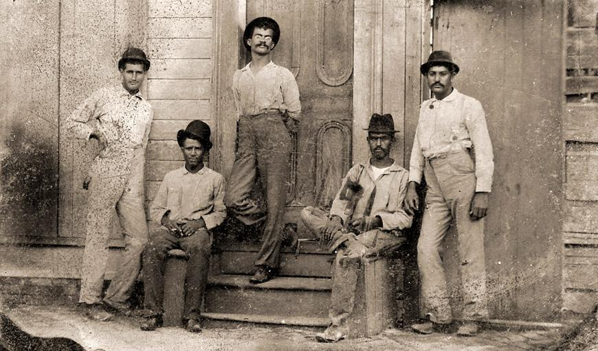 In this old fashioned, grainy, sepia toned photo, three men lean against a doorway, while two sit on a stoop. They wear black hats and stare straight at the camera.