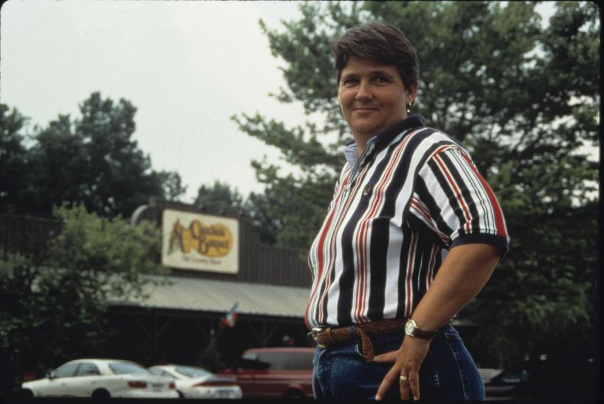 A white woman with short hair stands outside a Cracker Barrel restaurant and looks over her shoulder to smile toward the camera.