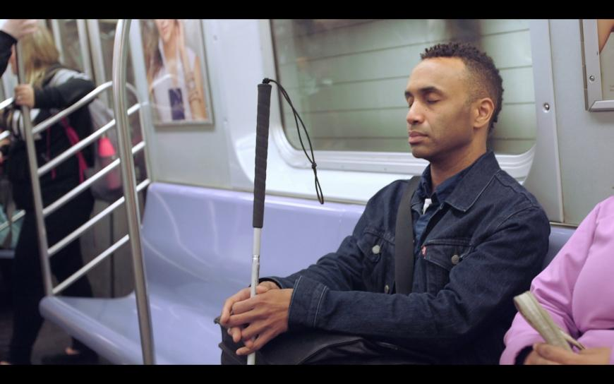 A still image from Vision Portraits shows Rodney Evans, a Black man, sitting on a subway. His eyes are closed, his face serene, and his fingers rest gently around his white cane.