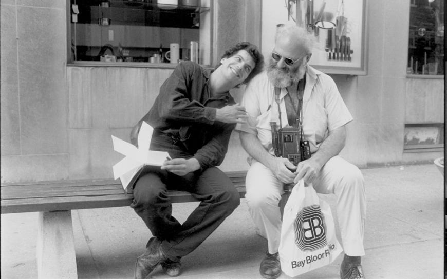 In this black and white photo, two men sit on a bench and smile at each other. On the left, actor Shane Fistell holds an open notebook on his lap and a pen in one hand. He lays his head on the shoulder of the famous physician Oliver Sacks. Dr. Sacks has a thick, white beard. He looks downward, wears a camera around his neck, and holds a white shopping bag.