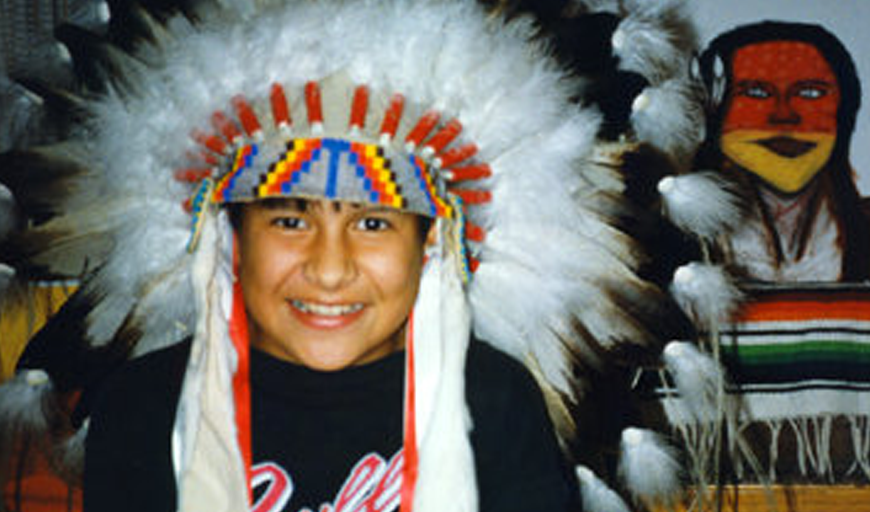 A child with brown skin wears a Native American feather headdress and smiles at the camera. Behind the child on the wall, a blanket and artwork depicting a Native person with long hair.