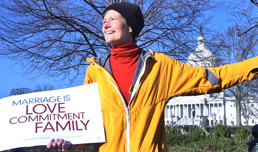 "Against a backdrop of a blue sky, bare tree branches and the US Capitol Building, a woman in a yellow coat smiles while looking off camera to the left.  She holds a sign that reads ""Marriage is love, commitment, family."""