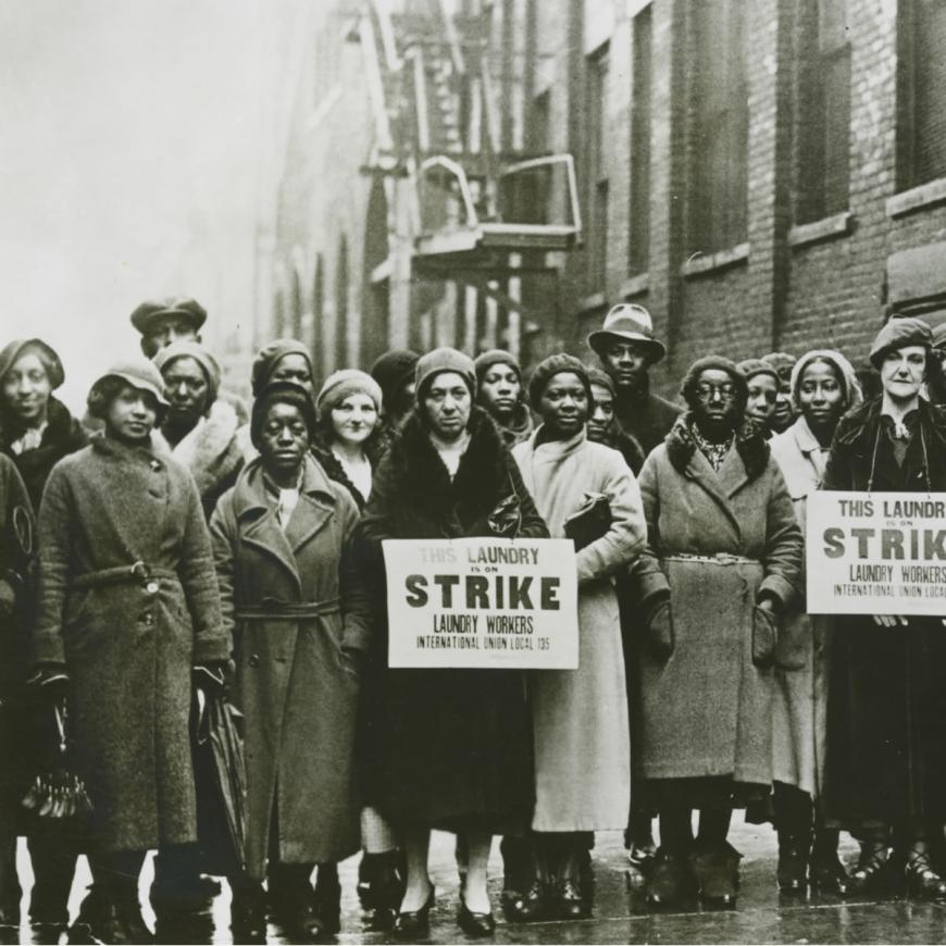 """Lines of protestors, mostly Black women, in long winter coats with somber looks on their faces. Two hold signs reading """"This laundry is on strike. Laundry Workers International Union Local 135."""""""
